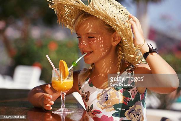 Portrait of girl with cocktail and straw hat