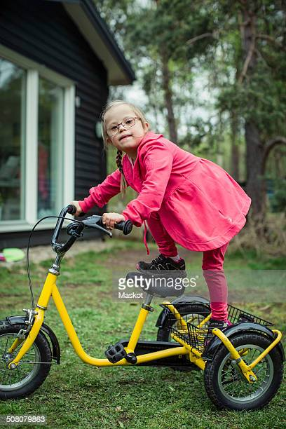 Portrait of girl with down syndrome balancing on bicycle in lawn
