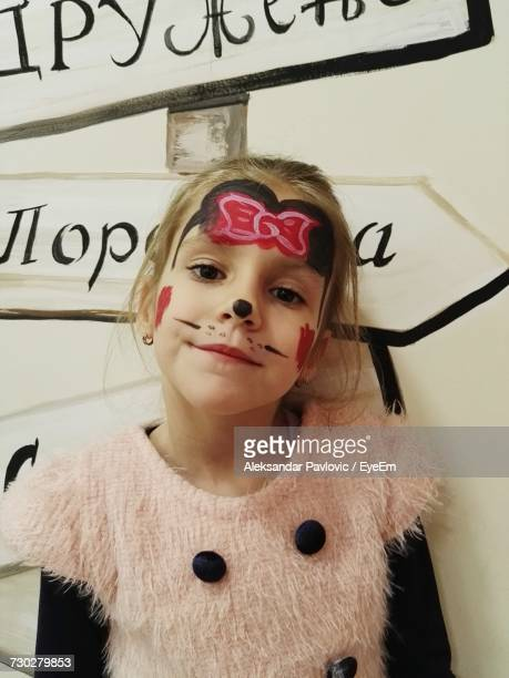 Portrait Of Girl With Face Paint Standing Against Wall