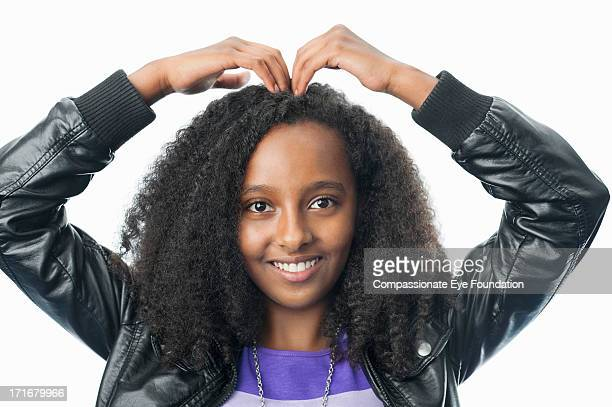 Portrait of girl with hands on head in heart shape