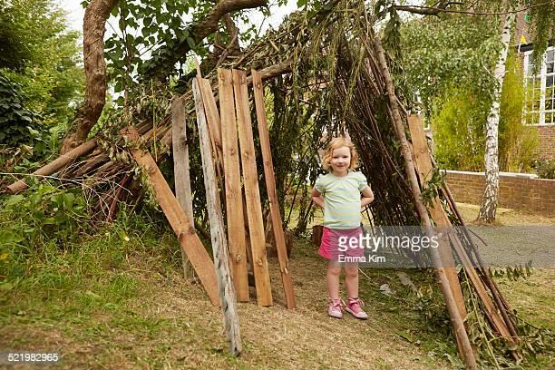 Portrait of girl with hands on hips in garden den