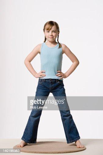 Portrait of girl (8-9) with hands on hips, studio shot