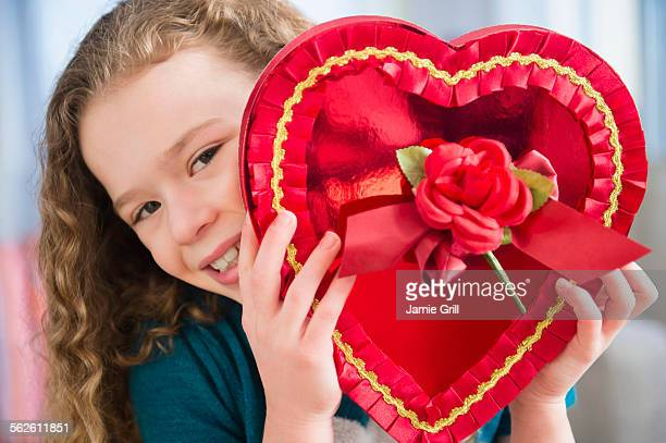 Portrait of girl (10-11) with heart-shaped chocolate box