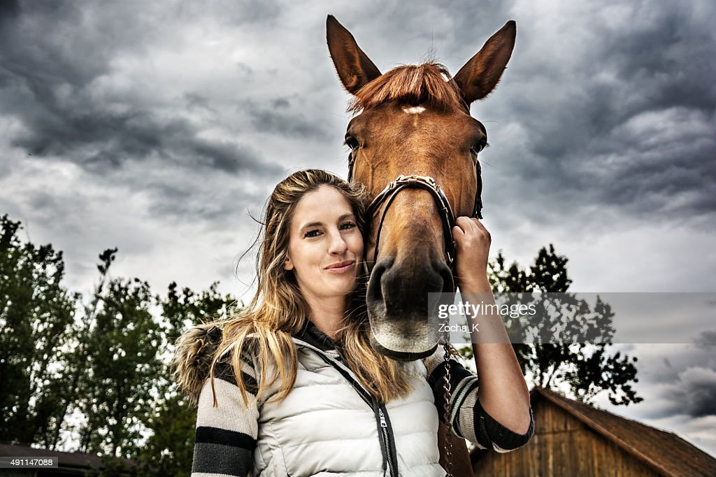 Portrait of girl with her horse on stormy day