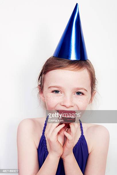 Portrait of girl with party blower wearing party hat