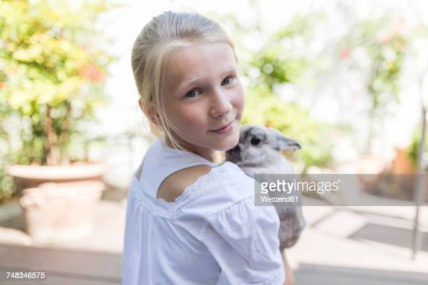Portrait of girl with rabbit outdoors