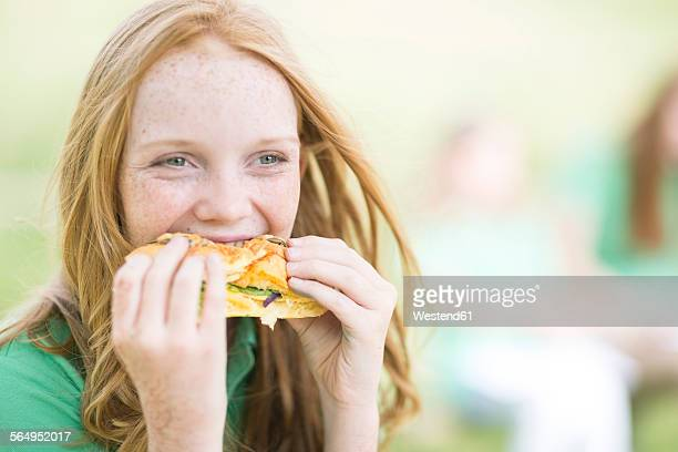 Portrait of girl with red hair eating a sandwich