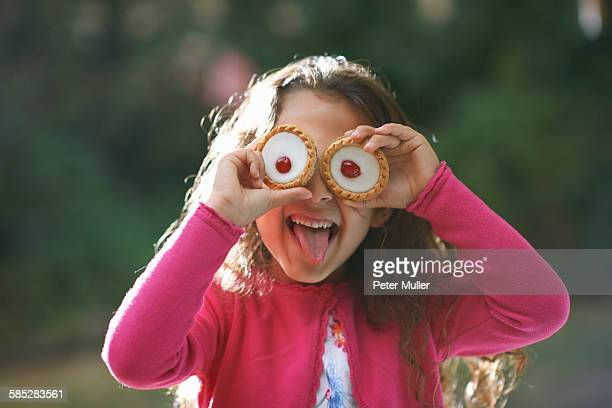 Portrait of girl with tartlets in front of her eyes in garden