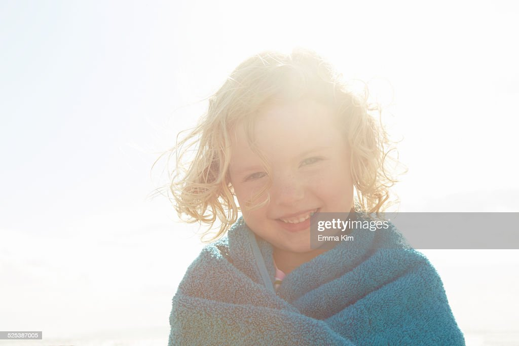 Portrait of girl wrapped in towel at sunlit coast