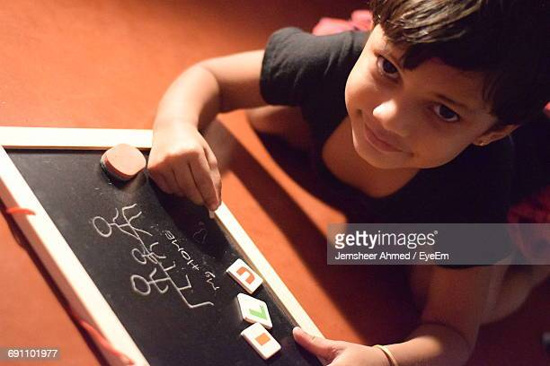 Portrait Of Girl Writing On Slate While Kneeling On Floor At Home