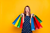 Portrait of glad, charming, pretty, crazy girl happy, excited that bought a lot of clothes at low prices, holding packets in two raised hands, isolated on yellow background, unbelievable shopping