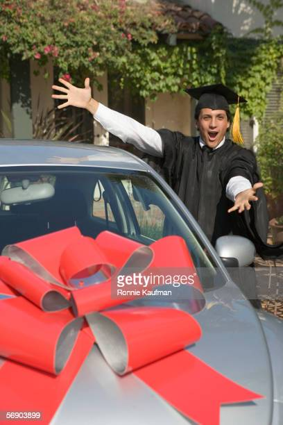 Portrait of graduating man with new car