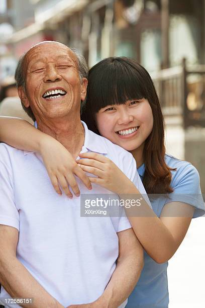 Portrait of grandfather and granddaughter together, outdoors in Beijing
