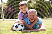 Portrait Of Grandfather And Grandson With Football Lying On Grass Smiling To Camera