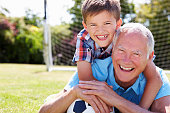 Portrait Of Grandfather And Grandson With Football Lying On The Grass Smiling To Camera