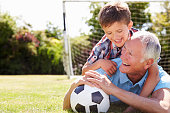 Portrait Of Grandfather And Grandson Lying On The Grass By Goal With Football Smiling