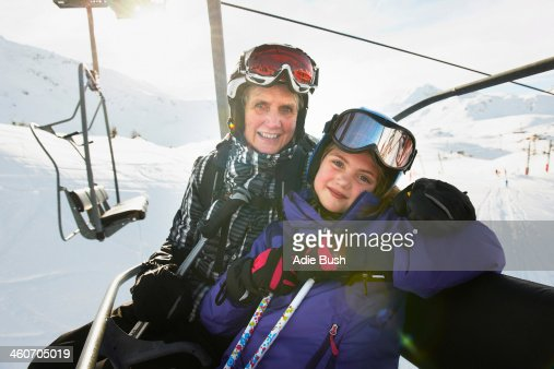 Portrait of grandmother and granddaughter on ski lift, Les Arcs, Haute-Savoie, France