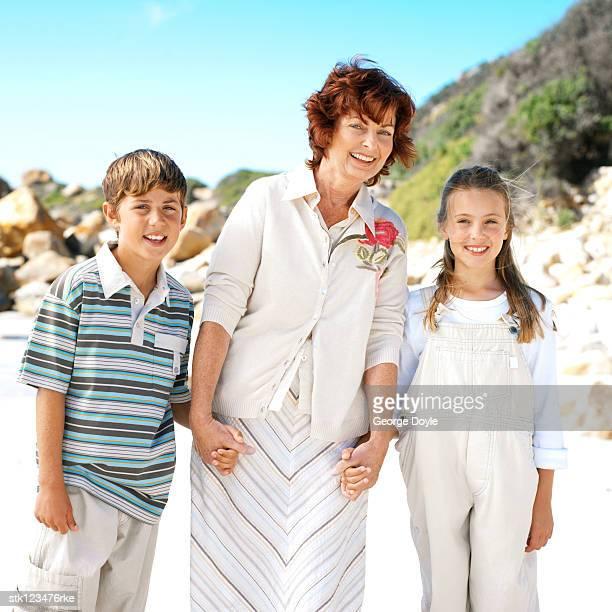 portrait of grandmother holding her grandchildren's hands