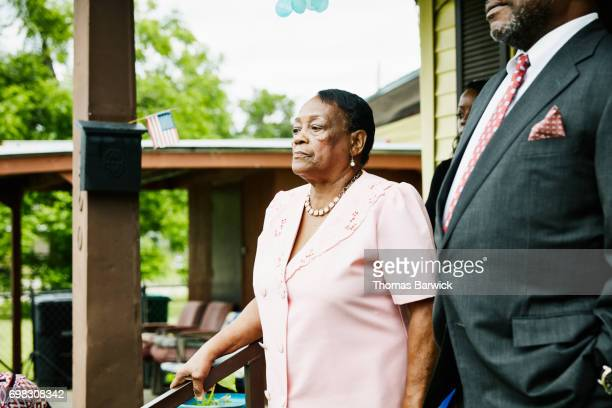 Portrait of grandmother standing on front porch dressed for church