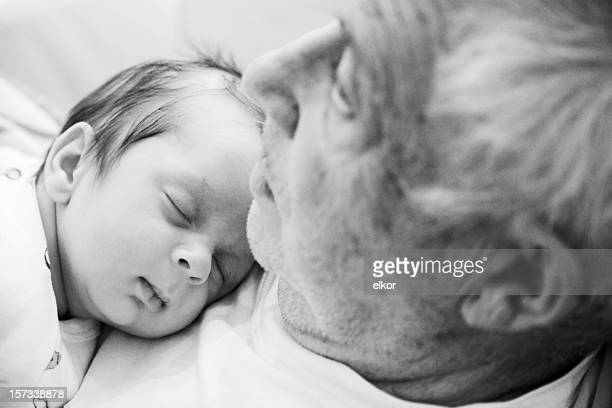 Portrait of grandpa with grandson sleeping in his chest