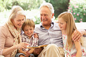 Portrait Of Grandparents Reading To Grandchildren On Sofa Smiling