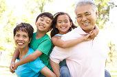Portrait Of Grandparents With Grandchildren In Park Smiling