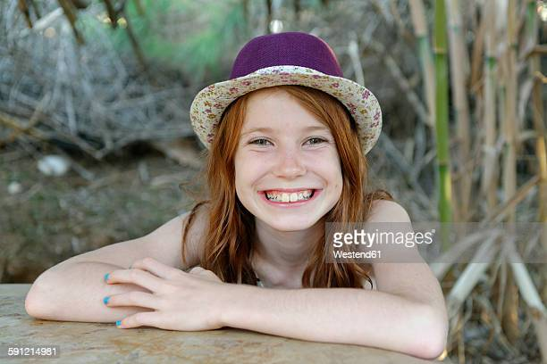 Portrait of grinning redheaded girl wearing hat