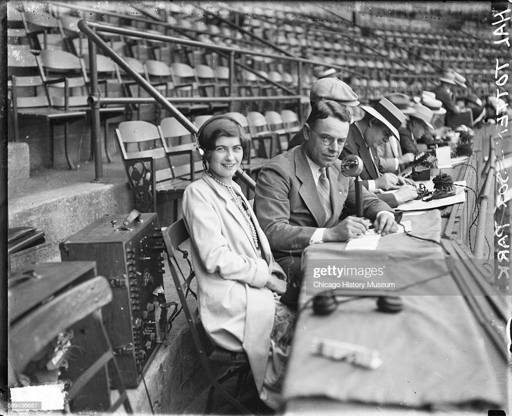 Portrait of Hal Totten sportswriter and White Sox and Cubs games broadcaster sitting with an unidentified woman at the announcers' table in Comiskey...