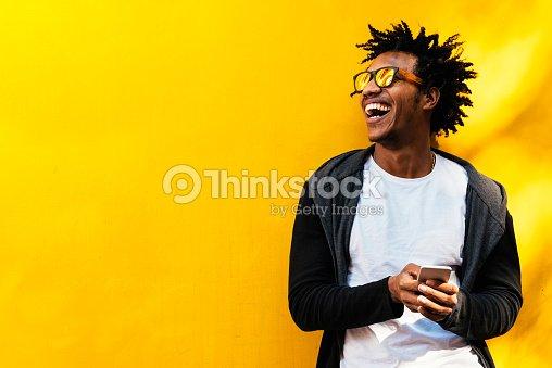 Retrato del guapo hombre afro con su teléfono móvil. : Foto de stock