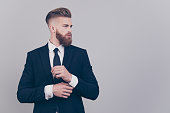 Portrait of handsome attractive neat elegant confident serious concentrated rich luxurious virile masculine boss chief fixing cuff-links on sleeve looking aside profile isolated on gray background