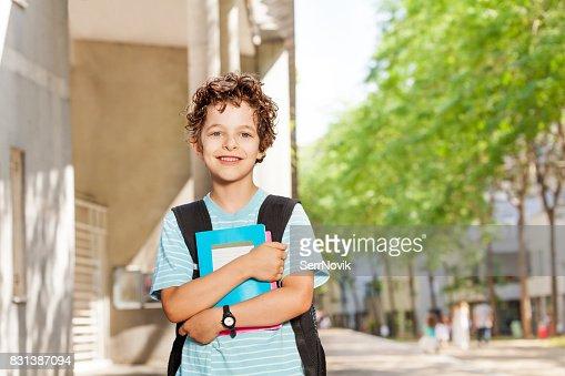 Portrait of handsome boy with books near school : Stock Photo