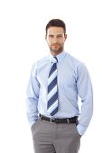 Portrait of handsome young businessman standing hands in pockets..