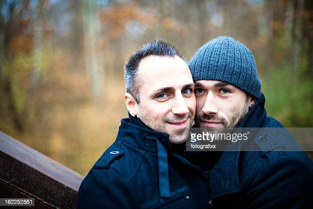 Portrait of handsome homosexual couple in front nature background
