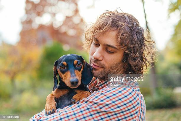 Portrait of handsome man and his dachshund dog in park