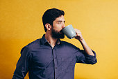 Portrait of handsome man drinking coffee over yellow background
