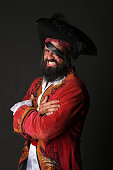 Portrait of handsome man in a pirate costume with hat and eye patch on black background