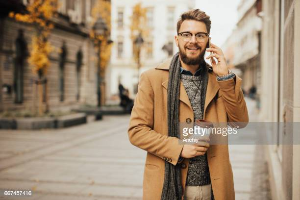 Portrait of handsome man in the city making a phone call