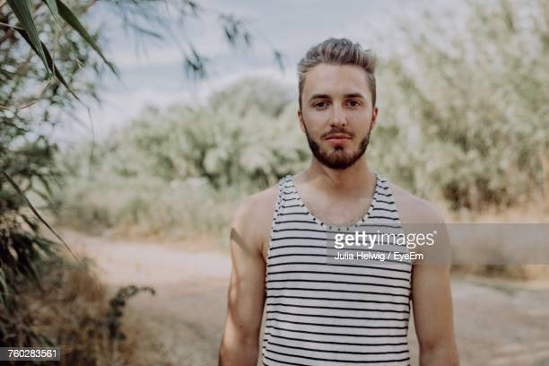 Portrait Of Handsome Man Wearing Striped Tank Top While Standing On Field