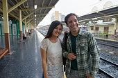 Portrait of handsome Persian tourist man and young beautiful Asian woman at the railway station Hua Lamphong in Bangkok Thailand horizontal shot
