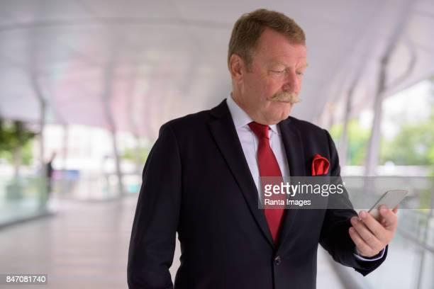 Portrait de bel homme d'affaires senior avec moustache relaxant à la passerelle à la ville de Bangkok en Thaïlande