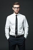 Portrait of handsome young businessman standing against dark gray background.