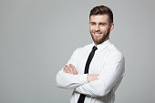 Portrait of handsome young businessman standing against gray background.