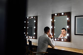 Portrait of handsome young man in white shirt looking into the mirror. Male reflection, light bulbs.