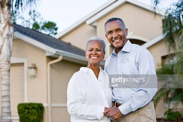 Portrait of happy African American couple standing outside home