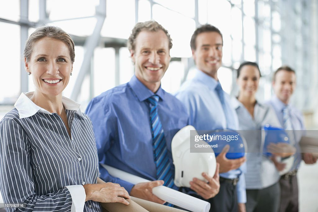Portrait of happy architects with hardhats and blueprints : Stock Photo