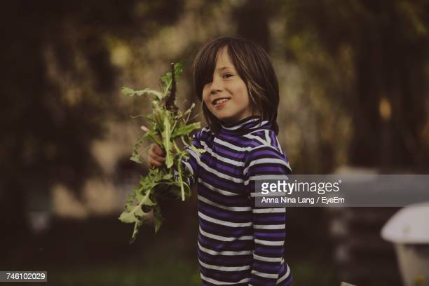Portrait Of Happy Boy Holding Plant