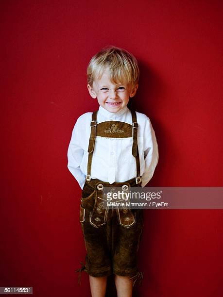 Portrait Of Happy Boy Standing Against Red Wall