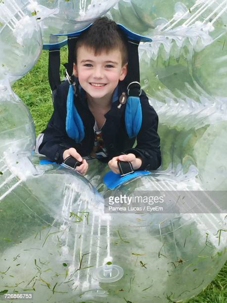 Portrait Of Happy Boy Zorbing At Park