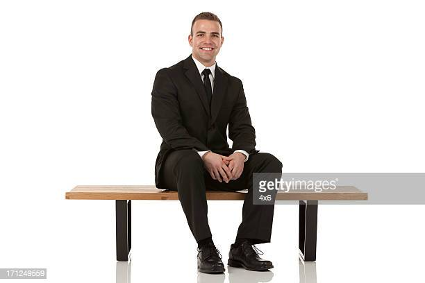 Portrait of happy bsusinessman sitting on a bench
