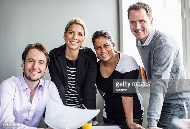 Portrait of happy business colleagues at desk in office
